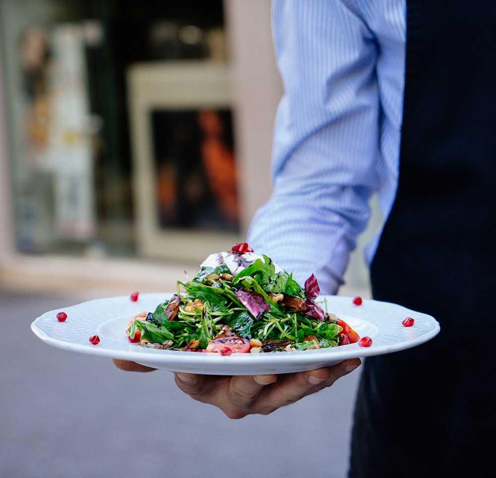 Service mit einem Teller Salad in der Hand.