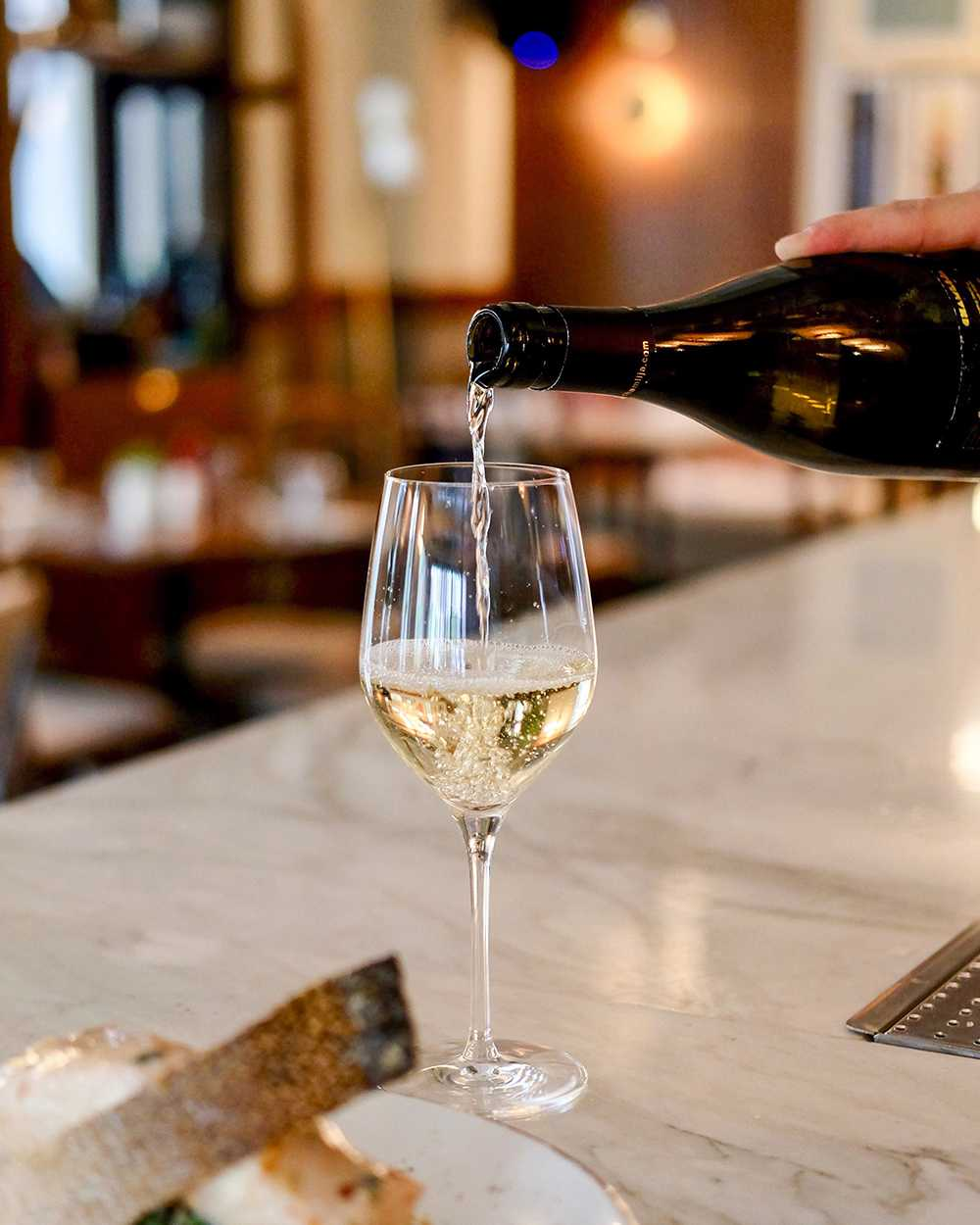 Weisswein wird in einem Weinglas einschenkent